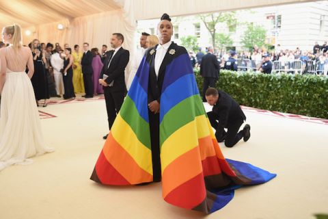 Black woman with black braids poses in black and white tuxedo with rainbow flag cape with black and brown stripes in front of people in multicolored formal attire on beige floor