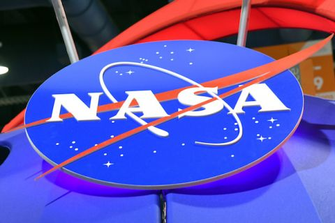 Blue circle with white text and dots and logo and red logo on blue plastic surface in front of red and black objects