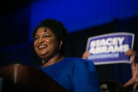 Stacey Abrams. Smiling Black woman in blue top stands at podium