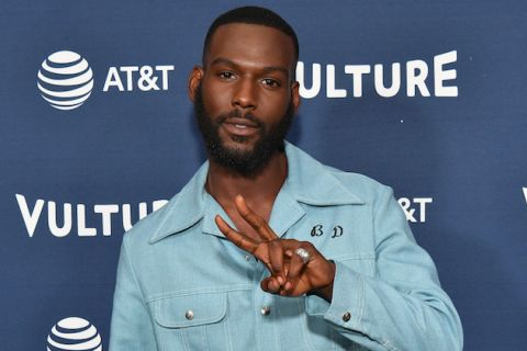 Black man with black hair and beard in blue shirt holds up two fingers in front of blue background with white