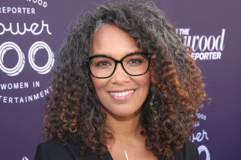Black woman in brown glasses and black blazer smiles in front of purple wall with grey text and logos