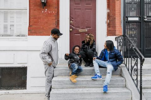 Black man in grey sweatsuit and black hat stands next to Black child in black jacket and blue jeans next to Black woman in black outfit next to Black woman in blue jacket and jeans on grey stoop by red rowhouse