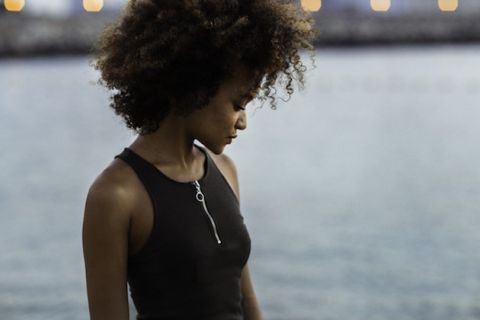 Black woman with brown curly hair looks sad in front of a body of water