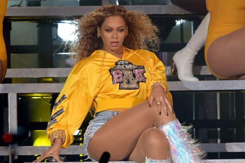 Beyoncé sits in yellow sweatshirt and blue jean shorts and blue and pink and white boots on grey riser in front of women in yellow and white outfits and grey wall