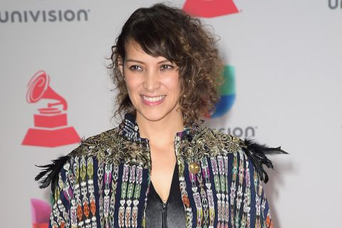 Gaby Moreno in black outfit with multicolored cover in front of white wall with black text and red and blue and green logos