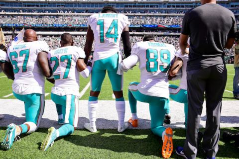 Laremy Tunsil, Maurice Smith and Julius Thomas kneel while Jarvis Landry stands in white football uniform with orange and light blue numbers and accents next to Black man in gray shirt and black pants on green field
