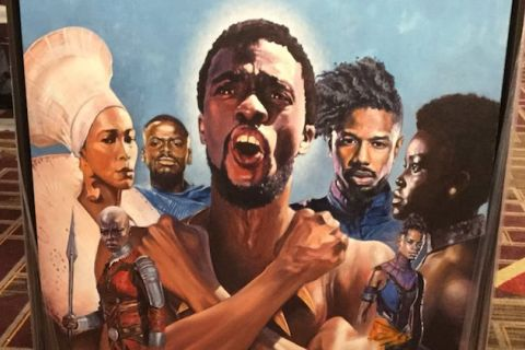 "Painting of ""Black Panther"" cast in multicolored clothing against blue sky on red and gold carpet"
