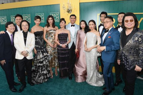 """Crazy Rich Asians"" cast and author on green carpet in multicolored formal attire in front of green and gold wall with gold text"