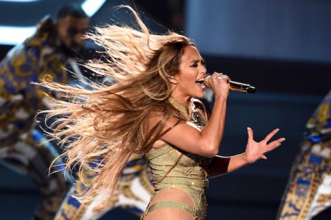 Jennifer Lopez's blonde and brown hair trails behind her while she performs in a gold outfit in front of backup dancers in white and gold outfits in front of a dark grey wall