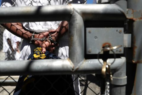 A person with their hands shackled behind their back is seen through an opening in a chain-link fence