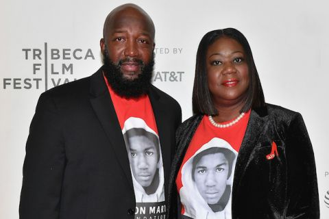 Tracy Martin and Sybrina Fulton in black blazers and red shirts with black and white image of Trayvon Martin stand in front of white wall with grey text
