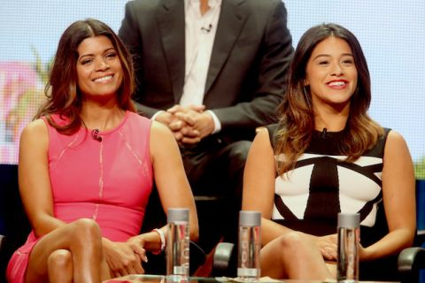 Andrea Navedo in pink dress sits next to Gina Rodriguez in black and white dress on black chairs in front of man in black suit with white shirt and light grey and pink screen