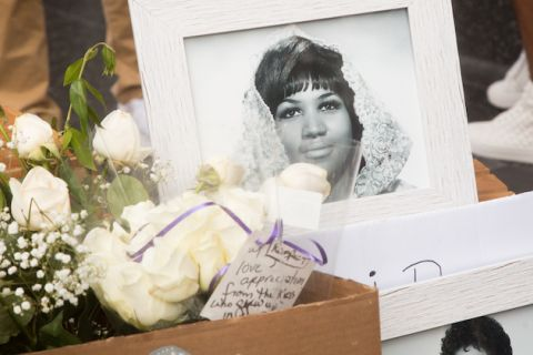 Black-and-white portrait of Aretha Franklin inside a white frame and surrounded by white notes with black text and green and white flowers on grey sidewalk in front of people in white shoes and brown pants