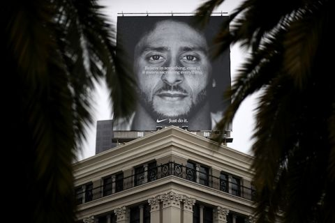 Billboard with black-and-white image of Colin Kaepernick and white text and Nike logo on top of beige building with black rails and windows behind dark green trees and grey sky