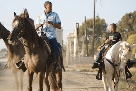 Black man in blue clothing rides brown horse next to Black child in black clothing on white horse in front of grey street and green trees
