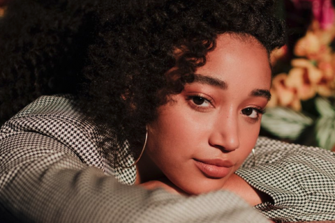 Amandla Stenberg in grey coat on red couch in front of green and orange wall