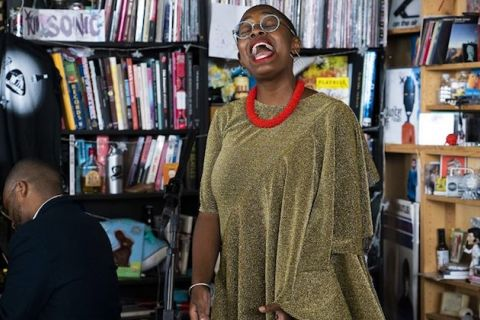 Cécile McLorin Salvant and Sullivan Fortner. Black woman in green shawl with red necklace and turquoise glasses sings behind black microphone and in front of a Black man in a black suit at a black piano in front of black and brown bookshelves
