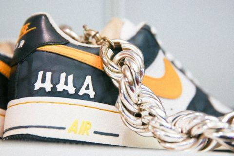 Hip Hop Archive and Research Institute sneaker with black and yellow and white details and white letters underneath rope chain in front of grey wall