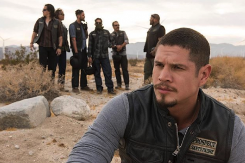 JD Pardo in black leather motorcycle vest with white and black patches and grey shirt in front of Latinx men in black motorcycle vests and dark pants and shirts on brown desert sand in front of grey sky