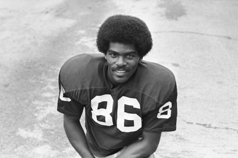 "Marlin Briscoe. Black-and-white image of a Black man with black afro and beard in jersey with white numeral ""86"" on front, in front of grass"