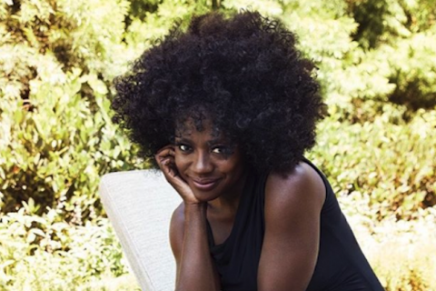 Viola Davis smiles in black afro and dress in front of green plants