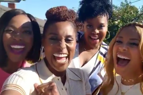 Black women of various shades laugh in the sunlight