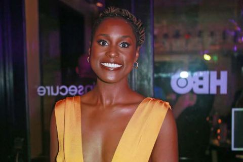 Issa Rae smiles in orange outfit in front of black doorframe and clear glass door with white letters and lights