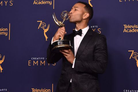 John Legend in black tuxedo holds and kisses gold Emmy award statue in front of blue wall with gold and white text
