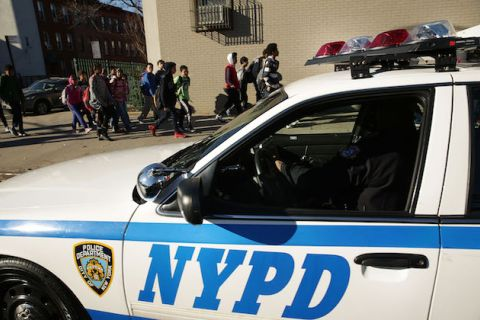 new york police department dispatch vehicle is parked outside of a school in the background students are walking