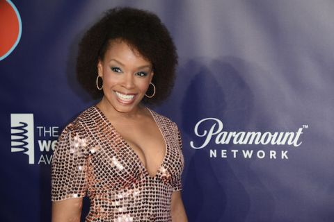 Amber Ruffin. Black woman with dark brown hair smiles in pink dress with rhinestones in front of purple wall with grey and white text and insignia