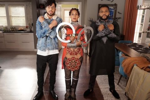 Marcus Scribner, Tracee Ellis Ross and Anthony Anderson. Black teenage boy in black pants and blue jean jacket and white shirt stands next to Black woman in red superhero outfit with silver rings next to Black man in black tunic with silver embroidery