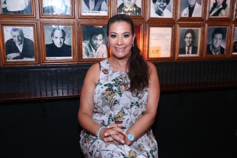 Maysoon Zayid. Brown woman in grey patterned dress with black hair smiles in front of black-and-white photos of comedians on brown wood wall above black siding