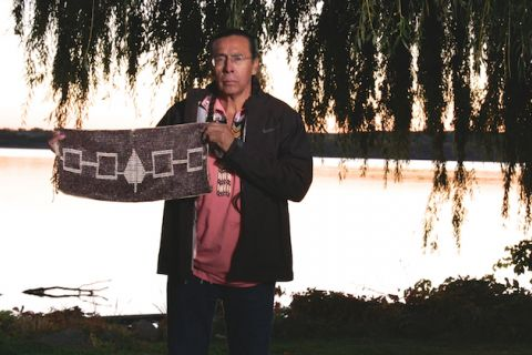 Sid Hill. Indigenous man in black jacket and red shirt holds grey and white Hiawatha Wampump Belt in front of lake and orange sunset and lakeside vegetation in black shadow