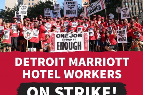 "Detroit hotel workers and their families holding picket signs reading ""One Job Should Be Enough"""