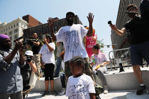 "A Black man wearing a white T-shirt that says ""Tamir Rice Only"" in black ink speaks at a protest"