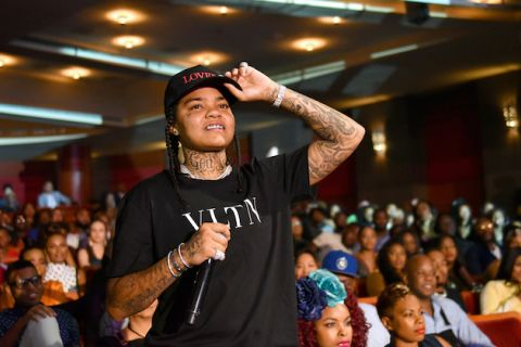 Young M.A. Black woman in black shirt and hat with black tattoos holds black microphone in front of Black audience inside red theater interior