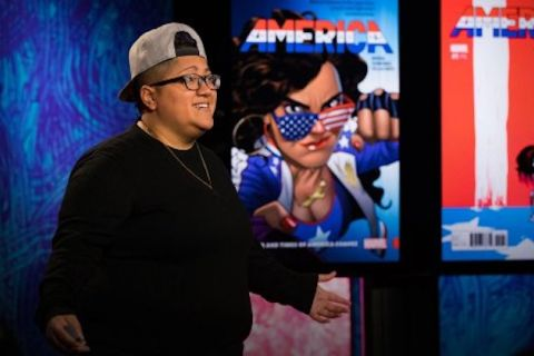 Gabby Rivera. Latinx woman in black shirt and glasses and grey baseball cap speaks into black headset microphone in front of blue background and multicolored comic panels