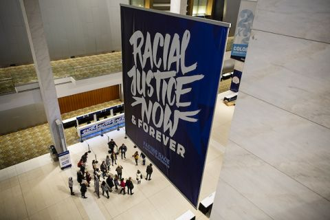 "A convention hall with a large navy blue banner that says ""Racial Justice Now & Forever"""