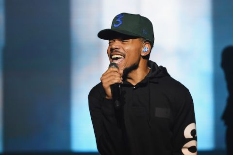 "Chance the Rapper. Black man in black sweatshirt and black hat with blue ""3"" performs while holding black and grey microphone in front of blue and white screen"