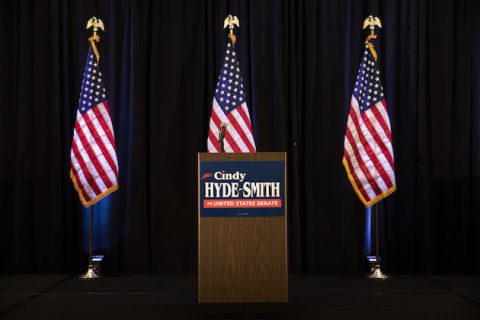 "Stage with brown wood laminate podium, red, white and blue sign on it reads ""Cindy Hyde-Smith for United States Senate."" Three American flags on poles behind it."
