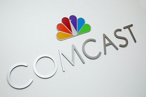"Silver letters spell ""COMCAST"" under multicolored NBC logo on off-white background"