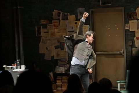 John Leguizamo. Latinx man with grey hair in brown suit and grey pants punches air in front of brown door and black wall with papers and grey desk with multicolored office supplies