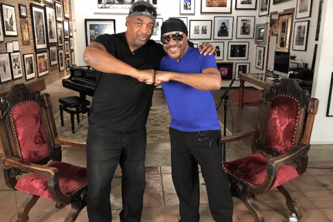 Chuck D and Ernie Isley. Black men in black pants and hats and blue and black shirts join fists in front of red and brown chairs and brown floor and white wall with multicolored photos and artwork