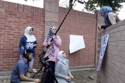 Muslim-American girls in white and gray and blue hijabs and multicolored clothing stand near Brown boy with black hair and beard and blue shirt while holding black filmmaking equipment in front of red brick wall and brown wall and green tree and gray sky