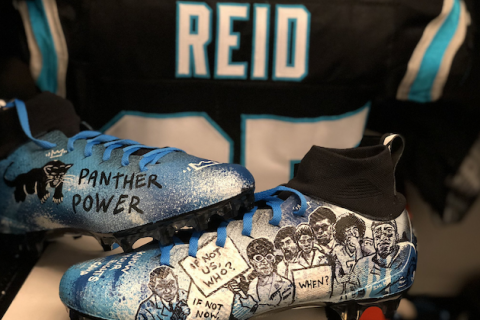 "Eric Reid;.blue and white football cleats with Black Panther Party symbol and protestors in black and white with text that reads ""PANTHER POWER"" and ""IF NOT NOW, WHEN?"" in front of black jersey with blue stripes and white letters that spell ""REID"""