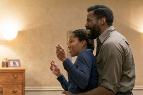 "Regina King and Colman Domingo in ""If Beale Street Could Talk."" Black woman in blue shirt and Black man in gray shirt dance in front of beige wall"