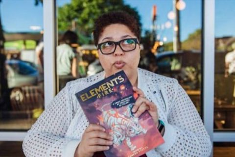 "Taneka Stotts. Black woman in grey sweater holds comic book with purple and pink cover and gold text spelling ""ELEMENTS FIRE"""
