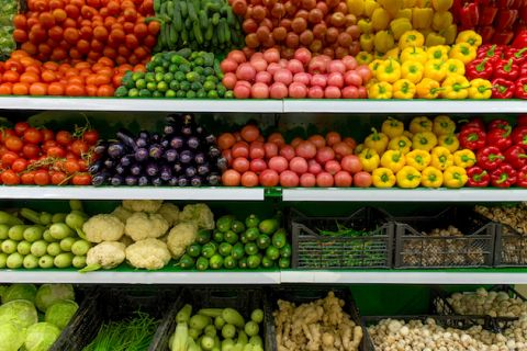 Wide angle shot of colorful produce stocked in a grocery store.
