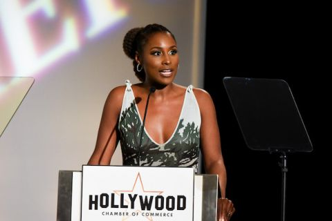 "Issa Rae. Black woman in green and grey dress speaks into black microphone on stand with white sign and back text reading ""HOLLYWOOD CHAMBER OF COMMERCE"" in front of black microphone and background with white text on screen"