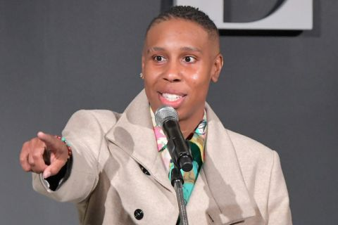Lena Waithe. Black woman in brown coat and pink and green and black shirt points and smiles while standing behind black and grey microphone and in front of dark grey wall with light grey portion of block letter